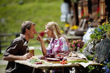 Österreich, Salzburger Land, Altenmarkt-Zauchensee, Paar bei Picknick auf Almwiese