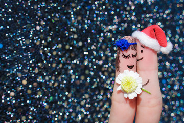 Face painted on the fingers.Man is giving flowers to a woman