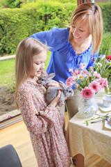 Mutter beobachtet ihre Tochter, die zwei Kaninchen hält