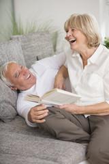 Lachendes älteres Paar mit Buch auf dem Sofa im Wohnzimmer