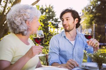 Mann und ältere Frau, beim Abendessen im Garten