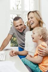 Glücklicher Großvater, Mutter und Sohn am Schreibtisch