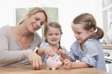 Mutter und Töchter, die Münzen im Sparschwein sammeln