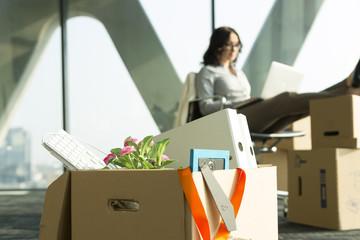 Karton auf Büroetage mit Geschäftsfrau im Hintergrund