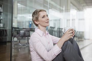 Geschäftsfrau im Büro, sitzt auf dem Boden mit Kaffeetasse