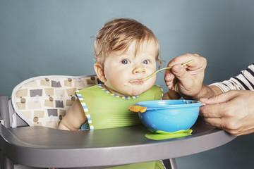 Baby in Hochstuhl wird gefüttert