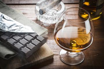 Cognac Cuban Cigar and Chocolat on wood background