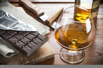 Cognac Cuban Cigar and Chocolat on wood background