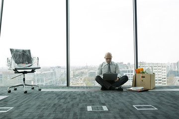 Geschäftsmann mit Laptop auf leerer Büroetage mit Karton
