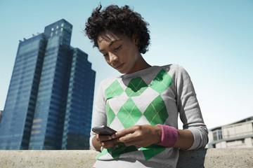 Junge Frau schaut auf Handy im Freien