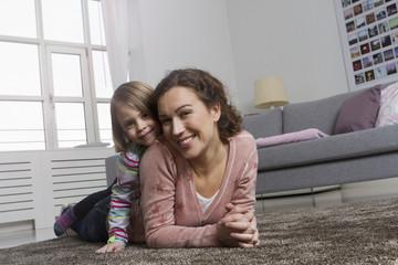 Glückliche Mutter und Tochter auf Teppich im Wohnzimmer