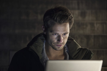 Junger Mann mit Laptop in der Nacht