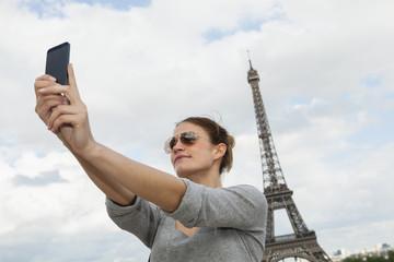 Frankreich, Paris, junge Frau fotografiert sich selbst mit Tablet-Computer vor Eiffelturm