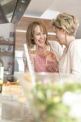 Zwei lachende reife Frauen mit Weißweingläsern in der Küche
