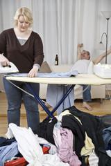Frau beim Bügeln, Mann im Hintergrund lehnt sich zurück