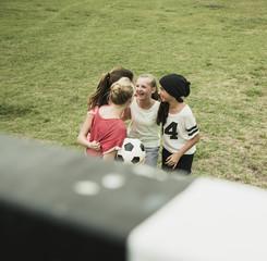 Vier Teenies, die Spaß auf einem Fußballfeld haben