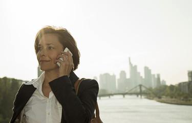 Deutschland, Hessen, Frankfurt am Main, Geschäftsfrau beim Telefonieren mit Smartphone vor Skyline