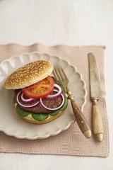 Burger mit Hackfleisch, Tomaten, Feldsalat und roten Zwiebeln auf Teller
