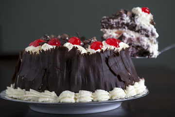 chocolate cake with cream and cherries, being served.