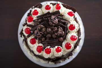 Chocolate cake with cream and cherries, from above.