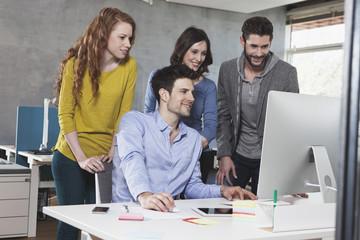 Desktop-Computer im Büro und vier Kollegen davor