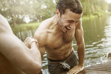Junger Mann hilft Freund am Steg aus dem Wasser