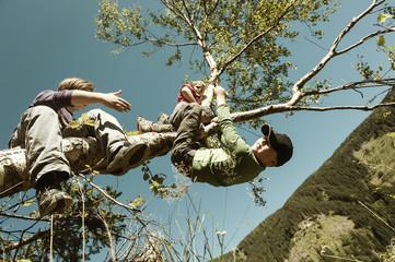 Zwei Jungen klettern auf Baum