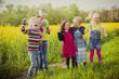 Sechs Kinder stehen vor der Rapsfeld