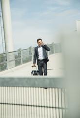 Geschäftsmann mit Rollkoffer, Telefonieren mit Smartphone