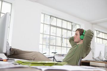 Junger Mann entspannt mit den Füßen auf seinem Schreibtisch