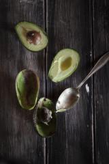 Löffel und in Scheiben geschnittene und ausgehöhlte Hälften von zwei Avocados