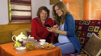 Smiling pregnant granddaughter show mobile phone to grandmother