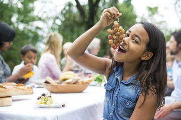 Mädchen isst Trauben auf einer Gartenparty