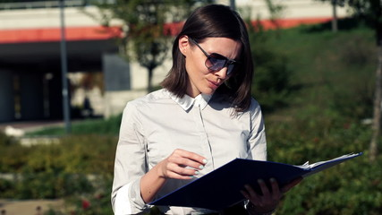 Young attractive businesswoman reading documents in the city