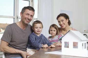Vierköpfige Familie mit Haus-Modell
