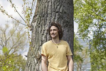 Lächelnder junger Mann am Baumstamm