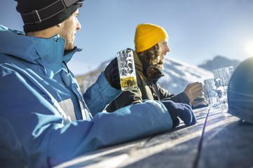 Österreich, Vorarlberg, Riezlern, Zwei Skifahrer im Biergarten