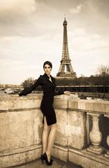 Frankreich, Paris, elegant gekleidete Frau posiert auf Brücke vor Eiffelturm