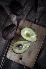 Scheiben und ganze Avocados auf Schneidebrett und Holztisch