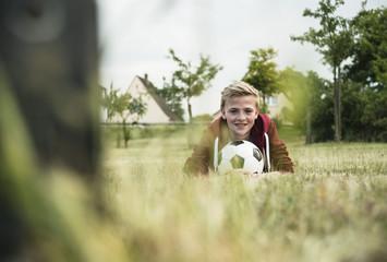 Teenager mit Fußball, liegt auf dem Rasen