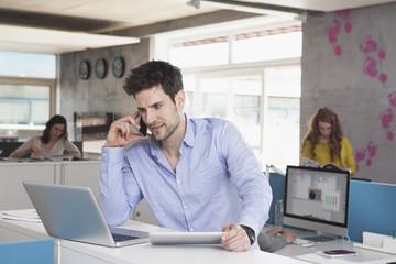 Porträt von Mann mit Laptop, Telefonieren mit Smartphone im Großraumbüro