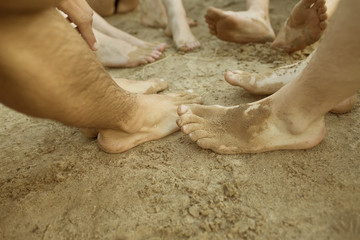 Füße von fünf Freunden im Sand