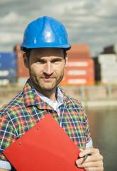 Mann mit Klemmbrett am Containerhafen