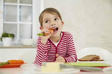 Deutschland, München, Mädchen sitzt am Tisch mit Bund Karotten auf dem Kopf