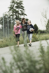 Drei glückliche Teenager-Mädchen mit Fußball und Skateboard