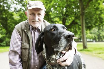 Älterer Mann mit seinem Hund (Deutsch Kurzhaar) im Stadtpark
