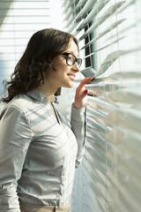 Geschäftsfrau schaut durch Jalousien