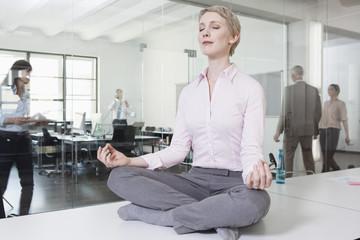 Geschäftsfrau im Büro, auf dem Schreibtisch meditieren