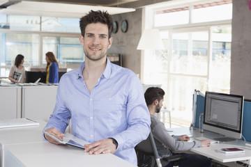 Porträt des lächelnden Mannes mit Tablet-Computer im Büro