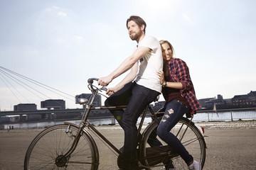 Glückliches Paar, Fahrradfahren am Flussufer